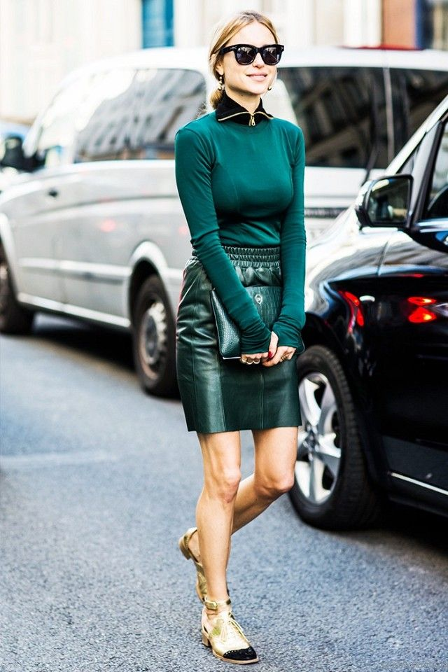 A layered sweater is paired with a leather skirt, cluth, and metallic cutout oxford shoes