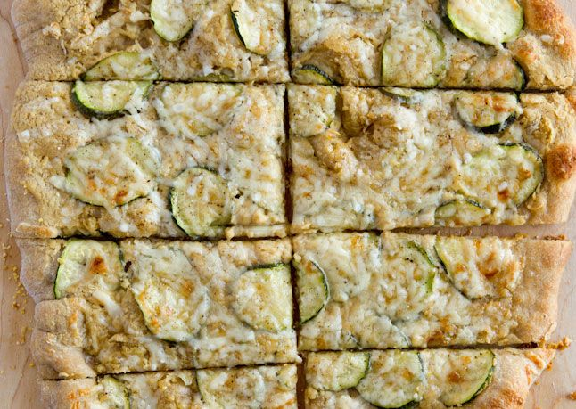 hummus and zucchini flatbread: brush whole-wheat pizza crust with olive oil, spread hummus on top, toss thinly sliced zucchini with grated onion and olive oil and spread in an even layer over hummus, sprinkle grated parmigiano-reggiano cheese on top, bake until crust is golden and cheese is melted and browned in spots