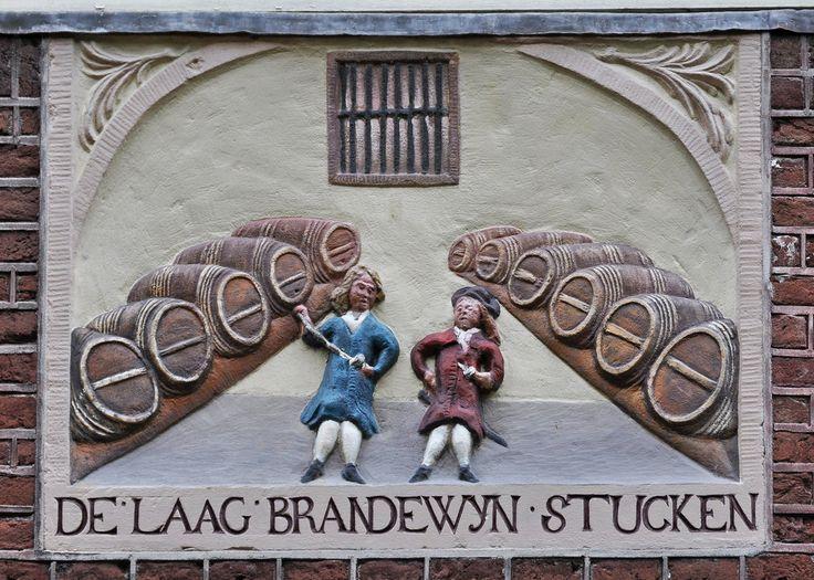 """Groenburgwal 37, Amsterdam De voorstelling op de gevelsteen, het interieur van een kelderruimte met twee mannen, de een met een wijnhevel en een glas, en aan beide zijden een stelling met (wijn)vaten, verklaart het woord """"laag"""" in het onderschrift. De Dikke van Dale leert ons dat een """"laag"""" een hoeveelheid van voorwerpen is die in min of meer horizontale richting ligt, zoals de vaten op de gevelsteen. Nu is het opvallend en wellicht niet toevallig dat het woord laag, maar dan als de naam ..."""