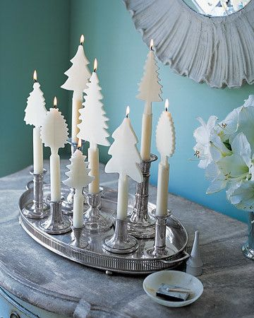 Candles adorned with beeswax trees create an enchanting winter landscape indoors.