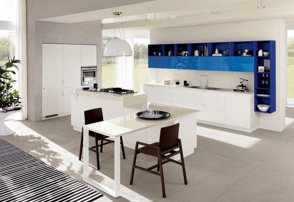 La #cucina Mood di Scavolini (design by Silvano Barsacchi) presenta un'inedita isola con zona cottura e tavolo incorporato con piani a due altezze. I moduli a giorno sospesi creano un'interessante cornice per i pensili, ideali per ambienti open space. Le ante delle basi, delle colonne e dell'isola sono impiallacciate in rovere bianco assoluto (come la struttura); quelle dei pensili sono laccati lucidi azzurro riviera mentre gli elementi a giorno sono laccati opachi blu.
