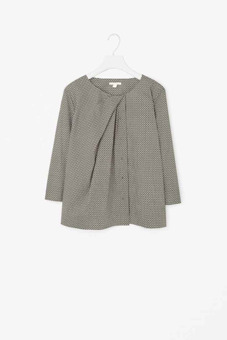 This shirt is made from soft cotton poplin with an all-over geometric print and asymmetric pleated neckline. A loose, boxy fit, it has wide 3/4 sleeves and a concealed button fastening along the front.
