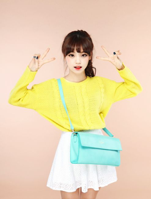 Cute spring look with the bright yellow sweater, pastel turquoise cross body bag, and a white skirt.