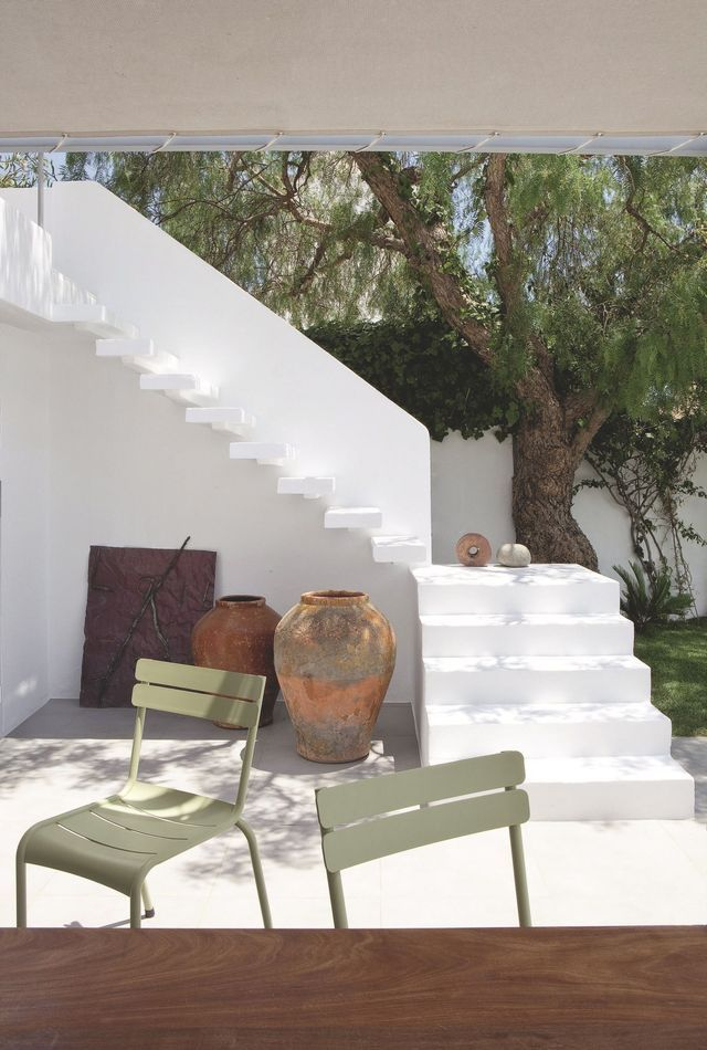 A dream villa on the Mediterranean. Outside happy marriage of architecture, sculptures by Martin Bialas, chairs Fermob and ibicenca jars.