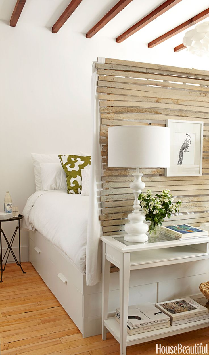 """Lathe walls enclose the sleeping area in a 400-square-foot Brooklyn apartment. """"Inside, it's hung with white curtains,"""" Lyndsay Caleo of The Brooklyn Home Company says. """"It's incredibly cozy, like you're in a nest, a cocoon, but it's still light and airy."""" The Brimnes bed from Ikea has drawers underneath, for more storage. """"We decided to define a sleeping area, because we felt people needed a private space,"""" says design partner Fitzhugh Karol.   - HouseBeautiful.com"""
