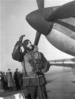 The pilot of a Spitfire fighter plane waves before taking off from a Royal Air Force fighter station.