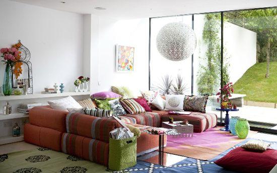 Leuke zithoek met veel kussens en een mix van tapijten op de vloer.
