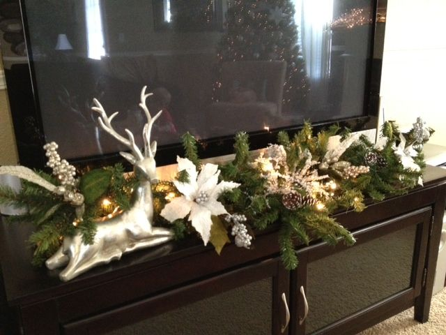 Garland in front of tv, would work as long as it doesn't edge into the frame.  (The BOYS would move it!)