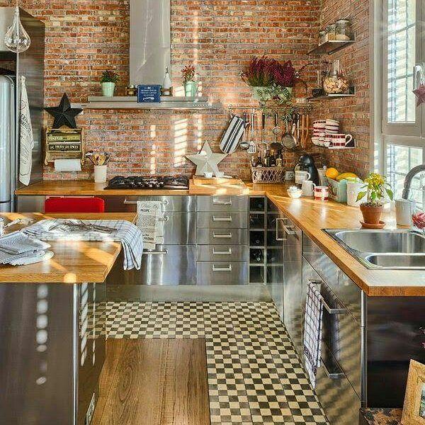 Cozinha com piso quadriculado, tijolo a vista nas paredes, bancadas em madeira, armários, cuba e coifa em aço inox.