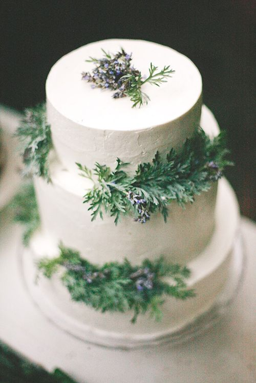 A three-tier white wedding cake with wintry evergreens | Brides.com