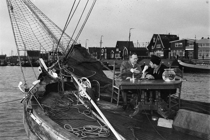"""VOLENDAM: WILLEN DUYS heeft vrijdagavond zijn """"Vuist"""" uitgezonden vanuit het visserdorp Volendam. Op de foto Duys (rechts met muts) in gesprek met een gast, met voor zich de traditionele vissenkom. 1968 #NoordHolland #Volendam"""