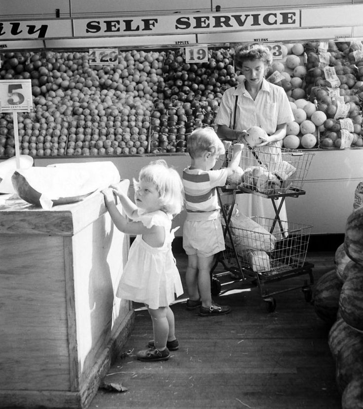 A mid-century mom and her two youngsters in the produce section of a grocery store!