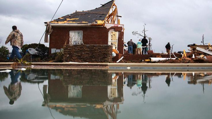 People are reflected in a swimming pool as they work to clean up at a home that was damaged by a tornado, Sunday, Jan. 22, 2017, in Adel, Ga. Gov. Nathan Deal declared a state of emergency in several counties, including Cook, that have suffered deaths, injuries and severe damage from weekend storms. (AP Photo/Branden Camp)