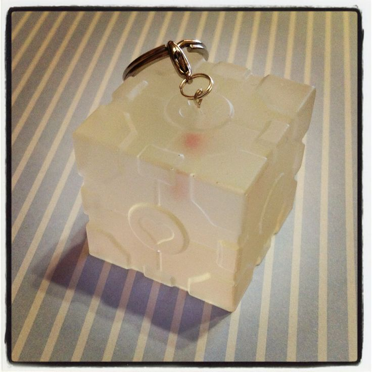 A Companion Cube from Portal! It is made out of resin, with a keychain attached so that it can be used to hang all your keys from! It can also be used as a paperweight!    At the bottom, the panel is clear and would revel the secret that is inside the Companion Cube!    An actual red heart candy ...