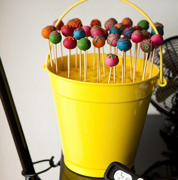 Na festa de aniversário, os pirulitos de chocolate foram servidos em um balde de alumínio colorido