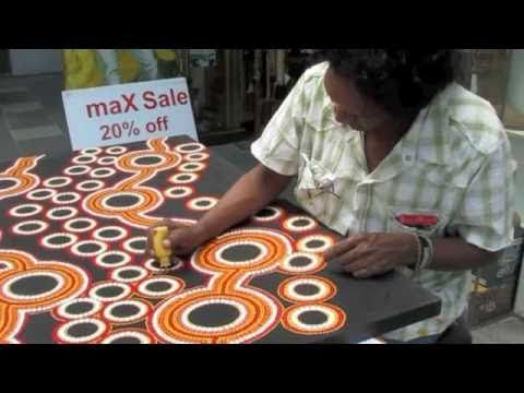 Aboriginal artist, John Turnbull, is shown here working on one of his dot paintings. He's using a bottle with a fine tip, another good way to make dots: