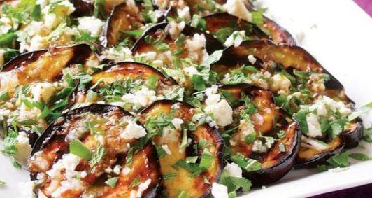 Μια εύκολη συνταγή για ψητές μελιτζάνες, περιχυμένες με σάλτσα βινεγκρέτ με σκόρδο και κύμινο, πασπαλισμένες με τυρί φέτα και μυρωδικά. Ο απόλυτος μεζές γι