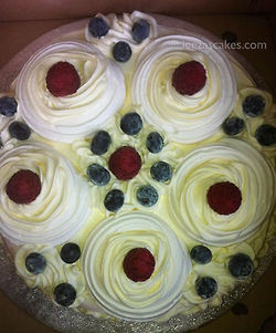 Large meringue gateaux with fresh raspberry and blueberries, fresh cream.