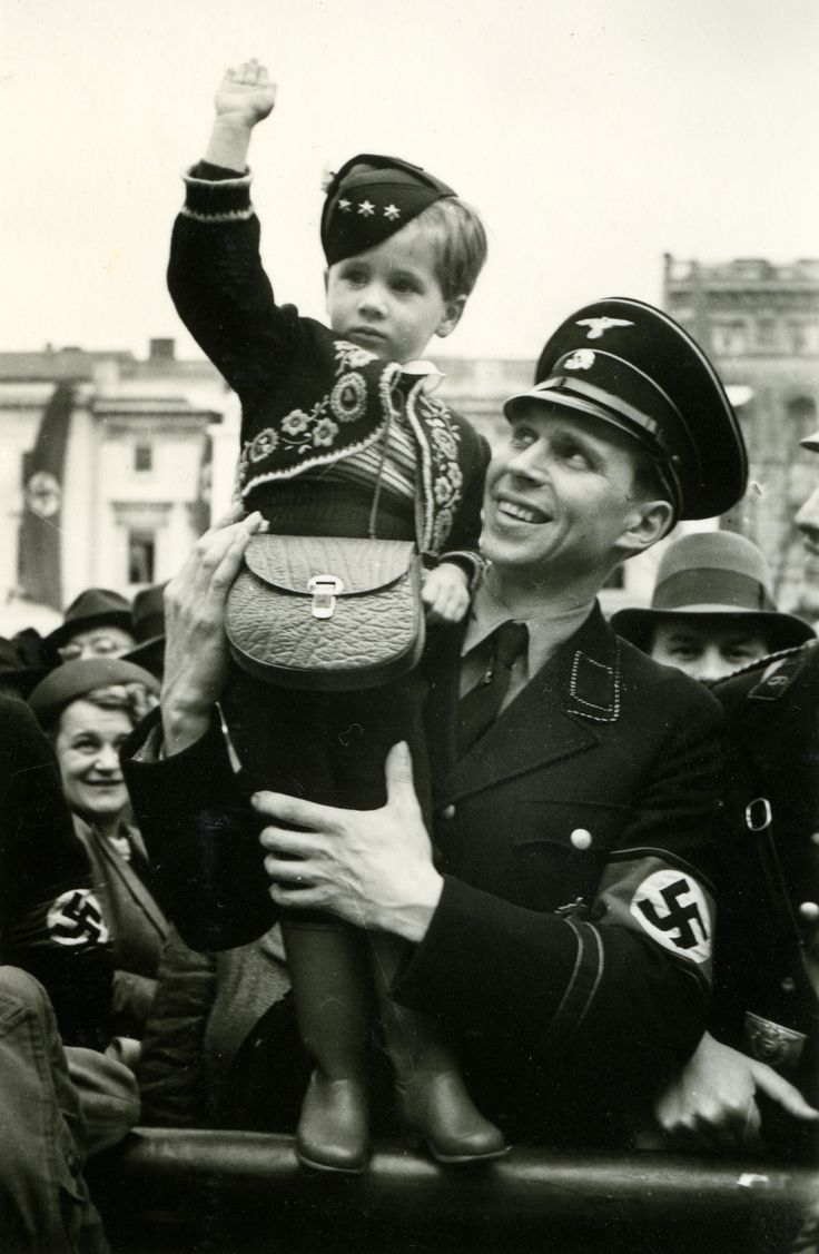"""The Banality of Evil: Ted Cannon was on his Mormon Church mission to Germany during the April 20, 1939 parade celebrating Hitler's 50th Birthday, and he photographed a young officer of the Allgemeine-SS holding his son dressed in a traditional German sweater jacket festooned with militaria-like pins and patches. The father is obviously proud that his little boy has learned to give the """"Heil Hitler"""" salute. One wonders just how many of the elated lemmings in the picture were dead six years…"""