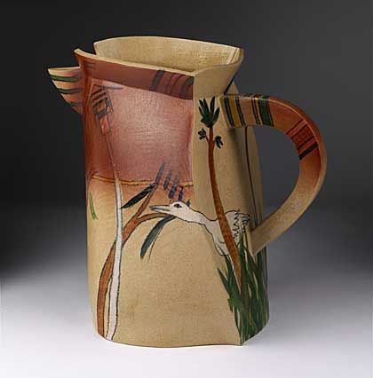 a flat brown jug with handle and stork and reeds motif