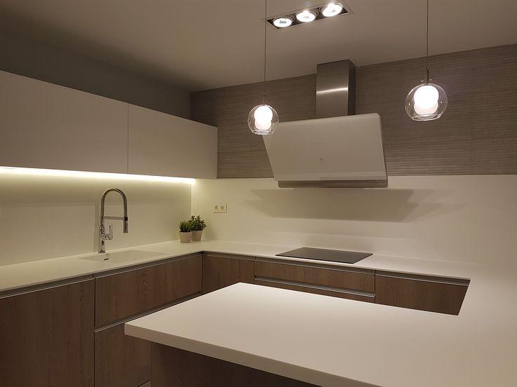 Cocina con barra en península. Encimera, fregadero y frente en solid surface. Revestimiento de pared en porcelánico efecto cemento rayado. Iluminación decorativa en cristal. Proyecto diseñado y desarrollado por AZ diseño.