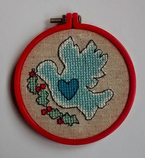 Gołąbek - ślub, święta, haft krzyżykowy. Haft na kanwie lnianej, średnica 8,2 cm (liczone z ramką), ramka w formie tamborka, czerwony plastik.