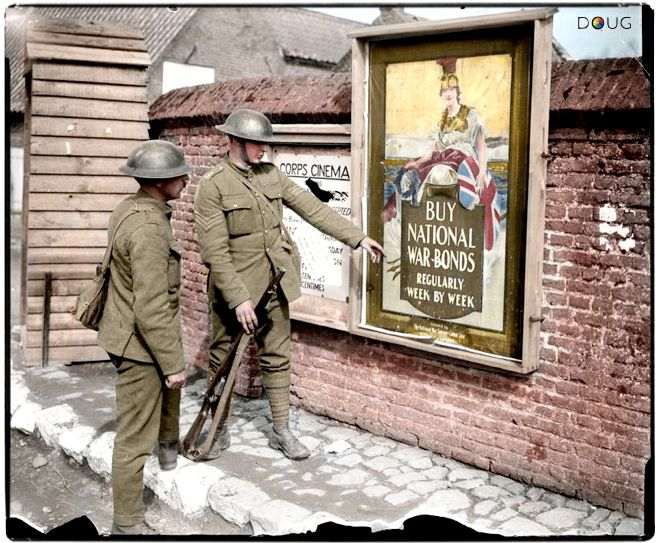 Two British soldiers pose by National War Bonds and Corps Cinema advertisements in Hinges, Pas-de-Calais, France on the 11th April 1918. The illustrated poster of interest, issued by the National War Savings Committee (Salisbury and London) reads 'Buy National War Bonds Regularly Week By Week', while a notice is relating to the opening times and ticket prices for the Corps Cinema.  © IWM (Q 6538)