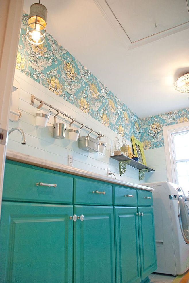 Yellow and teal wallpaper. Laundry room with bright turquoise cabinetry.