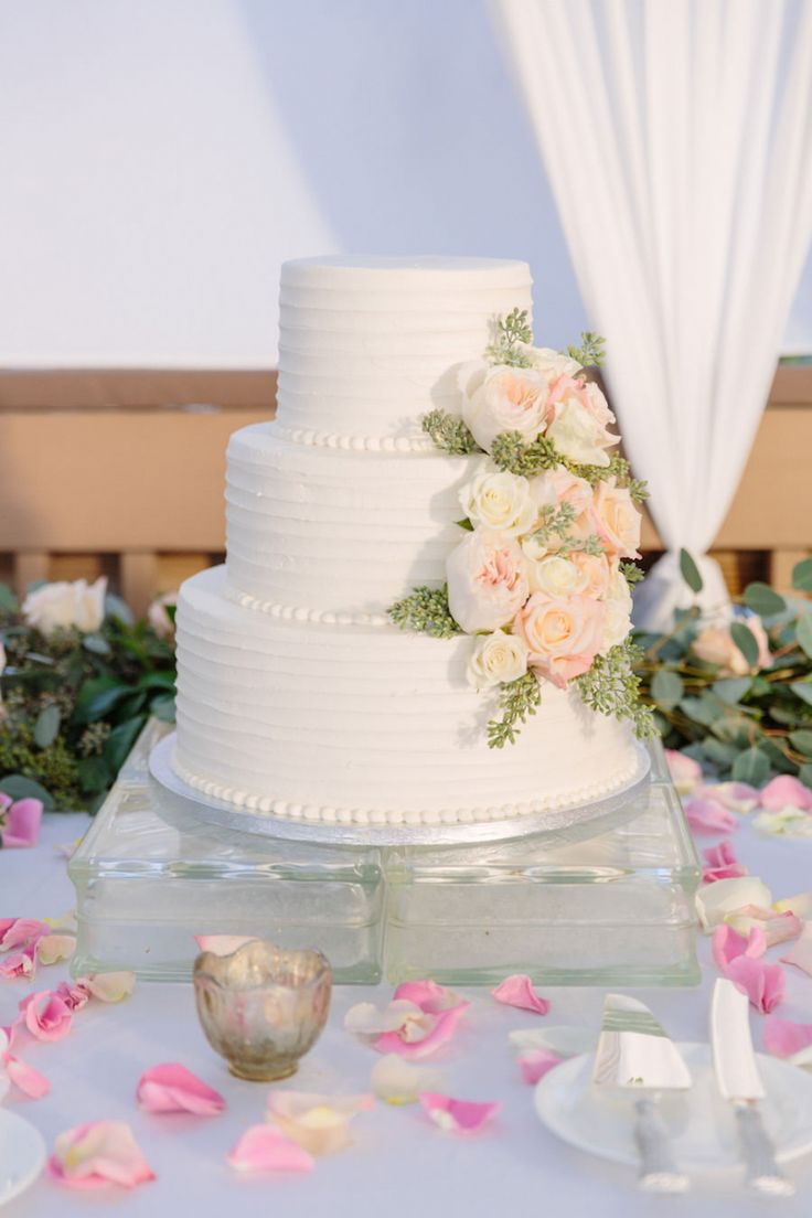 Love Wedding Cakes Three Tier Round White Cake With Real Blush And Ivory Ranunculus Greenery On Clear Glass Stand Rose Petals