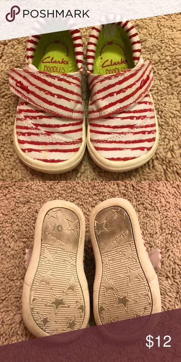Clarks baby shoes Red and white stripe clarks baby shoes. Size 4. Preowned and worn a few times but in great condition. Bottoms dirty bc they are white but could be cleaned. Velcro strap across front. Clarks Shoes Sneakers