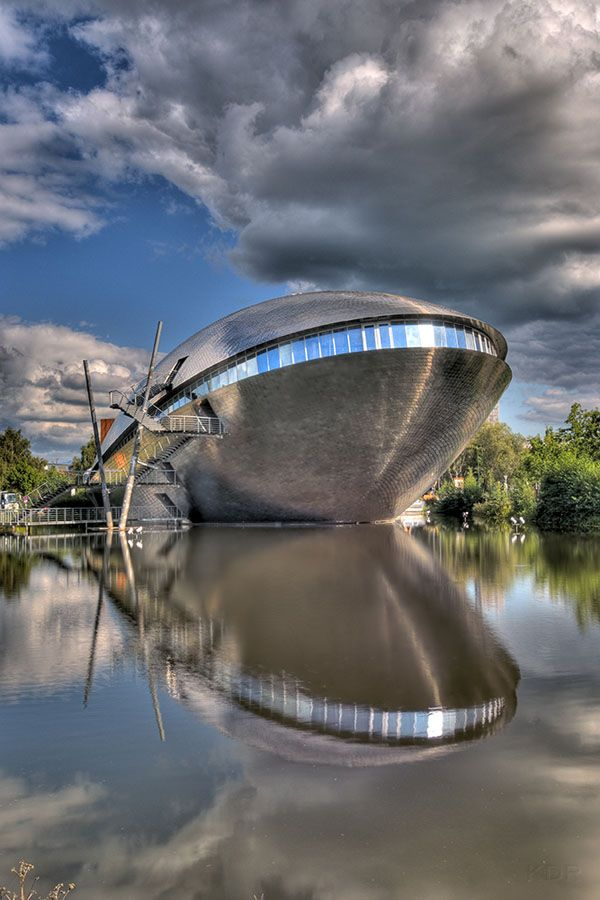 Bremen is a science museum located in Bremen, Germany that has around 250 exhibits. The building designed by Thomas Klumpp has an interesting shape that reminds of a grinning whale, an association that's reinforced by the water source it stands on.