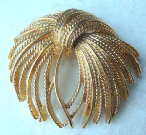 A stunning vintage draped textured spray brooch by Monet.   This large brooch is elegantly designed set in contrasting tone textured and plain gold tone metal., in a stunning design reminiscent of an exploding firework. Signed  Monet C to the back.  Circa 1960s -70's.