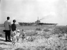 Visitors looking at the aircraft carrier USS Lexington docked in Pensacola, Florida.