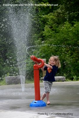 picture of child shooting water gun at the Waterworks Park Splash pad Waterworks Park- the flowers and frogs , etc.