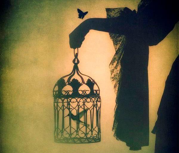 Mano agarrando una jaula con un pájaro