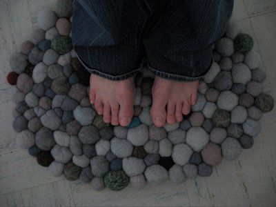 "There are some really good ""felted rocks"" tutorials on the interwebs. Pro tip: use uncolored core wool or felt batting on the inside because it's less expensive, and then needle or wet felt the colored wool on top. Craftster user Subloke was inspired by our March post about Ronel Jordaan's beautiful felted wool ""pebble carpet"" and ended up making her own version using"