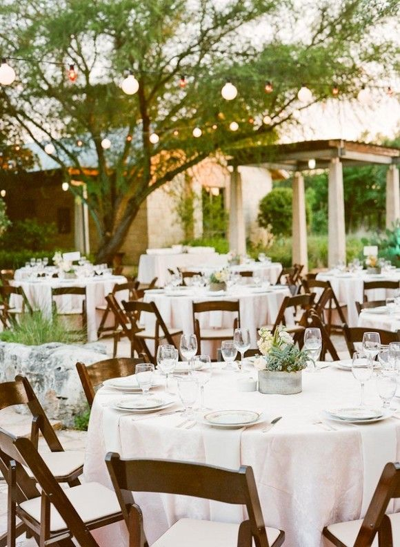 Simple white linens and wooden folding chairs help to capture the feel of a rustic wedding. Situate twinkle lights amongst the towering trees and place mason jars with wild flowers on the tables to establish a rustic feel.