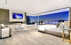 Bedroom ideas decor |  Modern spacious master bedroom design with extensive city views, floor-toceiling windows, small sitting area and large screen television mounted above a small gas fireplace.