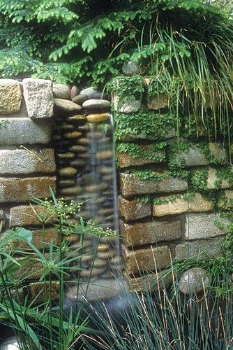 This brick wall frames a pebble water feature.