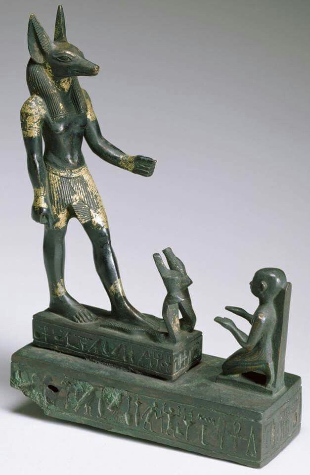 bronze statuette of Udja-Hor-resnet worshipping Anubis, dated to the 680-660 BC, now in the Walters Art Museum: in front of Anubis are the Two Uraei (representing the Two Goddesses Uadjet and Nekhbet) wearing respectively the Red Crown and the White Crown; the worshipper, Udja-Hor-resnet, with his back against an inscribed pillar which is pyramidal at the top, kneels before Anubis and extends his hands to the God palms down.