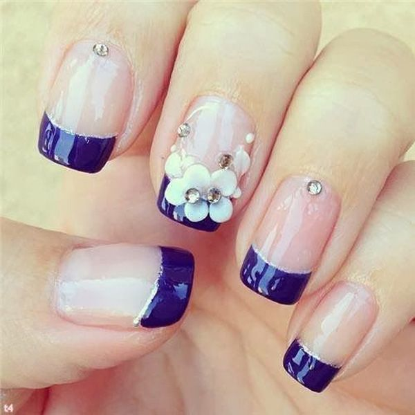 Glamorous looking blue French tip nail art design. Clear base coat is used with dark blue French tip. On top flowers and silver beads are added for accent.