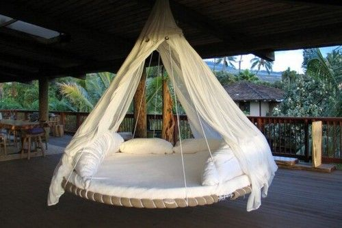 A hanging hammock made out of an old trampoline. As soon as I find someone to let me have their old trampoline, I will make this and add a few tweaks of my own. Add a few more pillows, change how the wires hold the hammock, and possibly a few out door lights and its the perfect hammock!