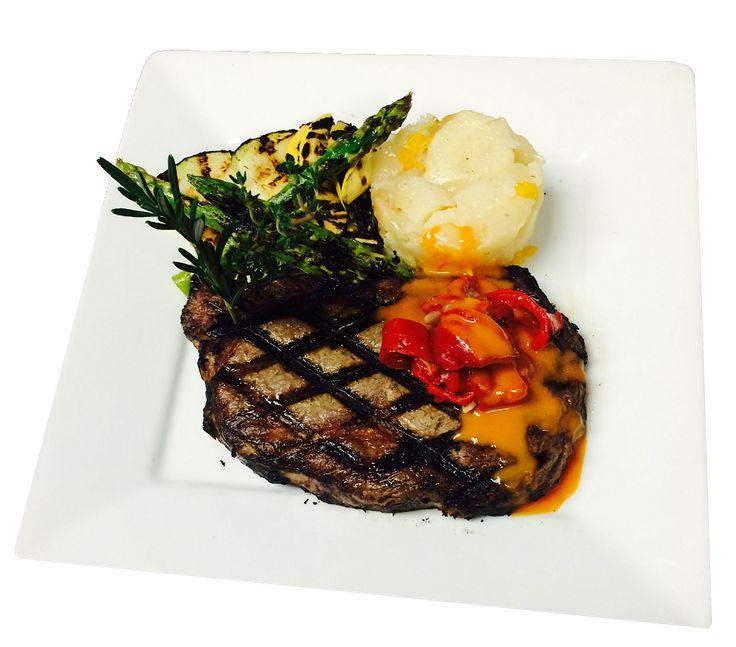 FILETE DE OJO A LA PARRILLA: Grilled Rib Eye Steak, Over Roasted Potatoes, Grilled vegetables & Peppercorn Sauce