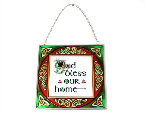 """This beautiful piece of window art features the phrase """"God Bless Our Home"""" in the center with intricate Celtic knots around the edges. The gorgeous colors in this stained glass panel will catch the light and create colored streaks of sun light in whatever room it's hung in. Window art features a lead glass look hung in a silver colored frame. Includes both a chain and suction cup for hanging. Imported by Royal Tara, one of Ireland's most well known companies that has been in the Irish goods…"""