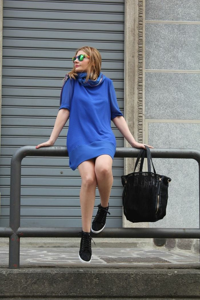 business casual dresses, blond woman with sunglasses, sitting on metal railing, wearing bright blue mini dress and black sneakers, holding large black bag