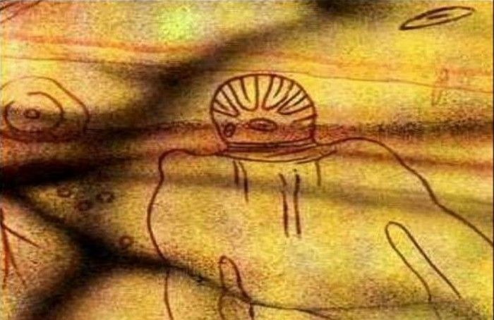 Рисунок на стене африканской пещеры изображает существо в головном уборе с антеннами, которое летает по воздуху. Существо имеет большие черные раскосые глаза, тонкие губы, и держит животное в своих руках.