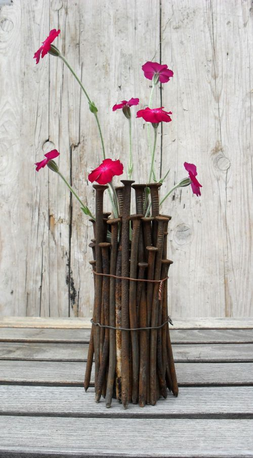 Rusty nails + bottle/vase, secure with wire. Tip: stick nails into sand to stabilize while working.