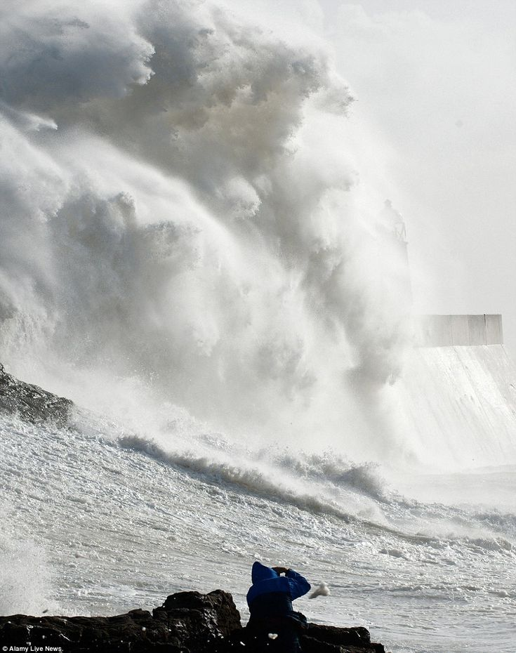 Capturing the moment: Photographers take a risk to get good shots of the storm waves at Porthcawl in Bridgend, South Wales