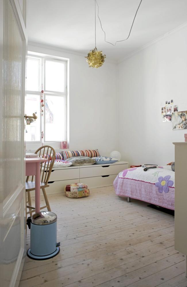 På pikerommet er både vegger og tak holdt i hvitt. Pastellfarger som rosa og blått er tilført via tekstiler og malte møbler. En oppbevaringsbenk med skuffer er dekket av puter, slik at den også kan brukes som sittebenk.