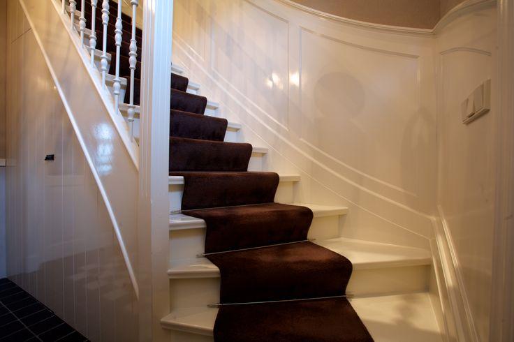 Hardhouten trap wit gelakt in Engelse stijl. Voorzien van loper. Afwerking wanden met lambrisering meelopend in de lijn van de trap.